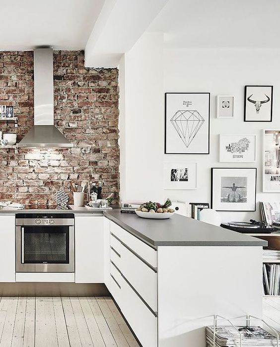 a white kitchen with grey countertops is refreshed and enlivened with a red brick wall