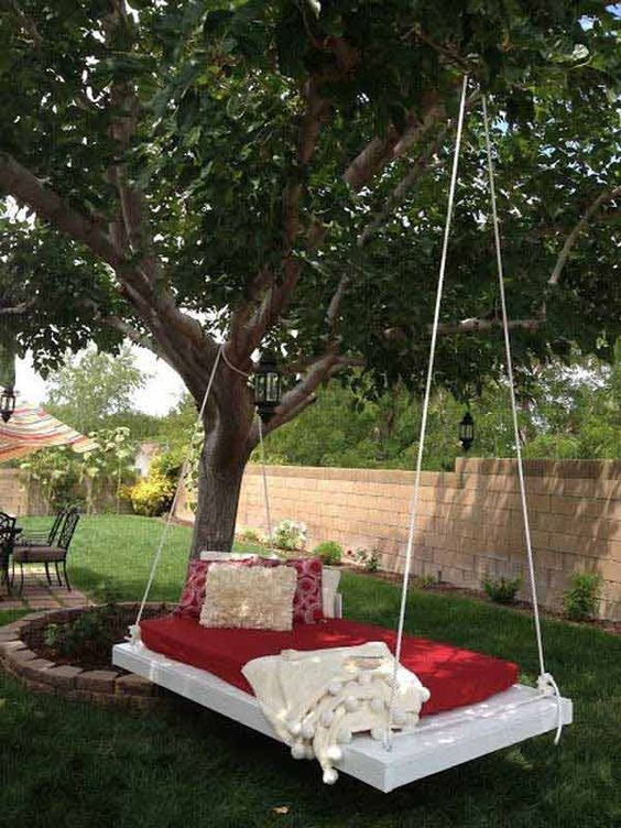 a whitewashed hanging bed on ropes with colorful bedding and pillows is a cool idea for outdoors