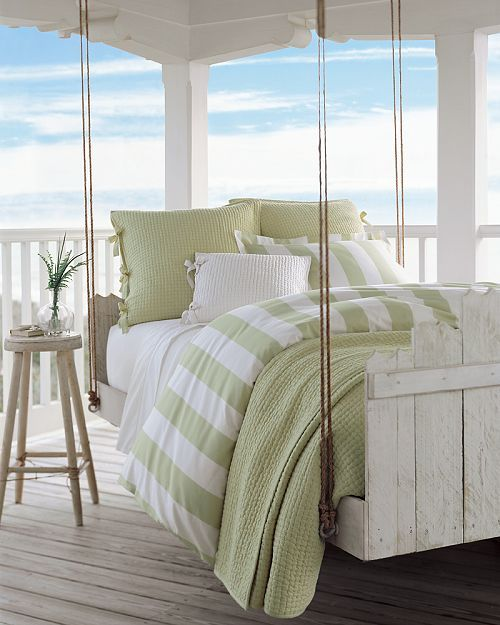 a whitewashed hanging wooden bed on ropes with a matching stool and green and white bedding looks very inviting