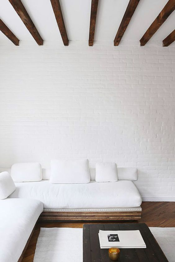 an airy and serene living room with white brick wlals, an L-shaped sofa