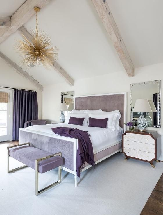 an eclectic bedroom with a lavender bed and an upholstered bench, a sunburst chandelier, wooden beams and purple and white bedding