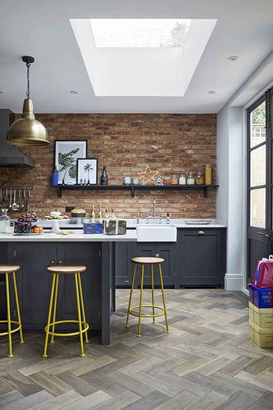 an eclectic kitchen with graphite grey cabinets, white countertops and red walls plus brass touches