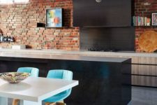 an eclectic kitchen with sleek light and dark cabinets, a red brick wall and bright turquoise chairs