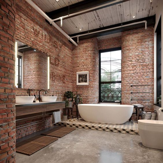 an industrial bathroom done with red bricks, a concrete floor, a tiled platform and chic modern appliances