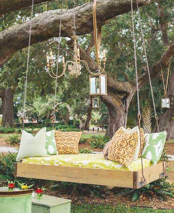 an outdoor hanging bed for one, some lanterns and ropes for decor and printed pillows is a bright idea