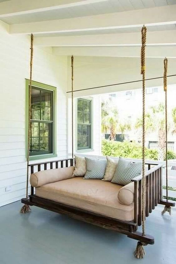 an outdoor hanging bed of dark stained wood, ropes with neutral and printed bedding and pillows is a great porch piece