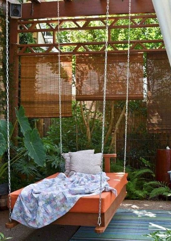 an outdoor hanging bed on chains with bright bedding, blankets and pillows is a fit for a tropical space