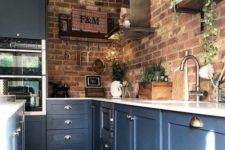 blue kitchen cabinets with white countertops and red brick walls is a bold contrasting idea with a touch of chic