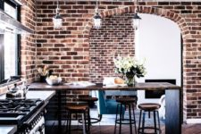 bold red brick walls, stained chevron clad floors and rich stained furniture for an industrial meets rustic kitchen
