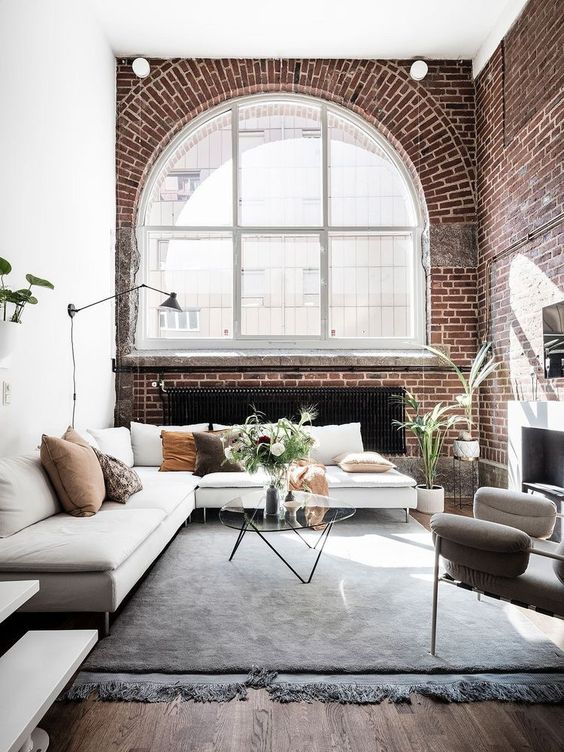 make your living room more luxurious with red brick, arched windows and a variety of textiles