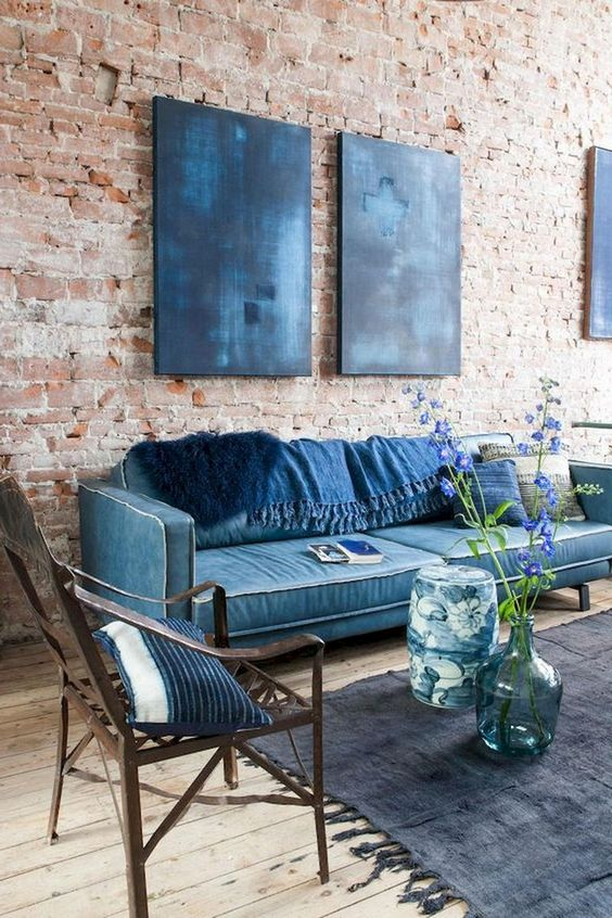 navy furniture and pillows plus artworks contrast the red brick wall and a wooden floor