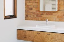red brick paired with green geometric tiles, a light-colored vanity and a white countertop look chic and bold