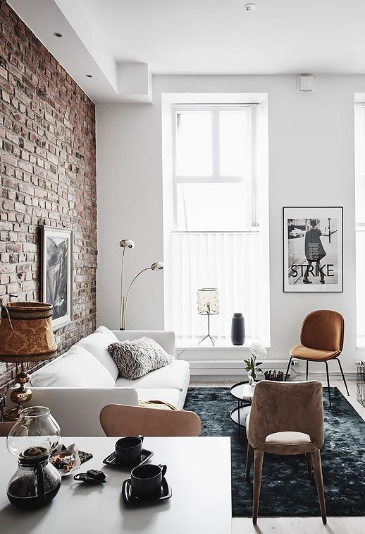 the exposed brick wall gives the living room a lot of character already, which is enhanced by the contrasting black and white