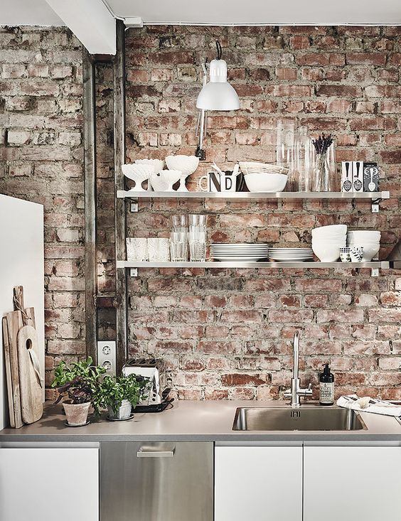 white and shiny metal kitchen cabinets and red brick walls that make the space look more distressed and relaxed