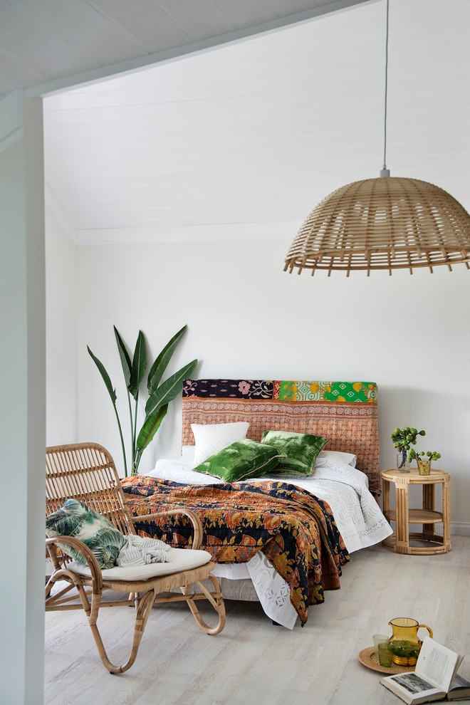 a bright tropical bedroom with a pink upholstered bed, a rattan chair, a wicker lampshade and bright bedding  (Bowerhouse)