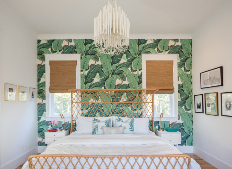 a tropical meets glam bedroom with wicker shades, a rattan bed, a glam chandelier and a statement tropical print wall  (Margaret Wright Photography)