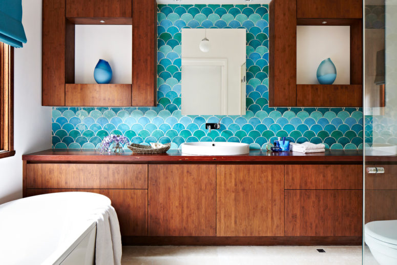 a beautiful sea-inspired bathroom with rich-stained wooden furniture, turquoise and blue fish scale tiles and an oval bathtub  (Camilla Molders Design)