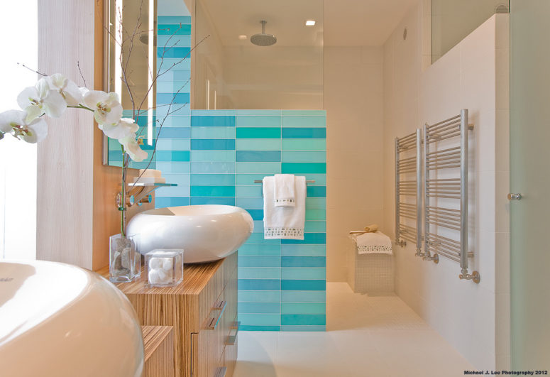 a luxurious sea-inspired bathroom in neutrals and blue and turquoise tile wall plus orchids  (Light Positive)