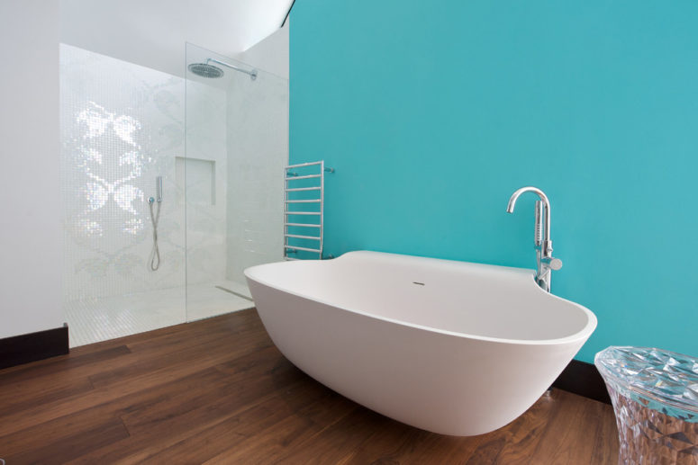 a minimalist ocean-inspired bathroom with a statement turquoise wall, a catchy-shaped tub and mosaic tiles in the shower  (Yorkshire Design Associates)