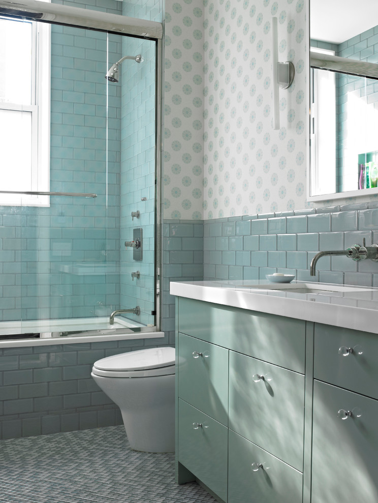 a sea-inspired bathroom with aqua and turquoise colored tiles and cabinets, printed wallpaper  (Rusk Renovations)