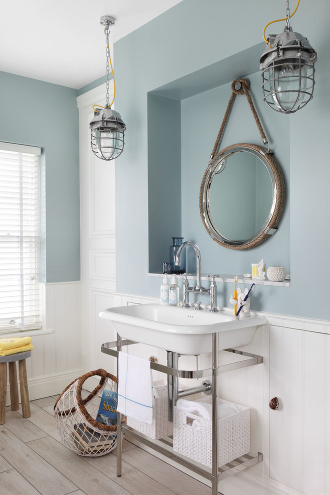 a nautical bathroom with a slate blue half wall, a vintage sink, vintage pendant lamps and a wooden floor  (Oliver Burns)