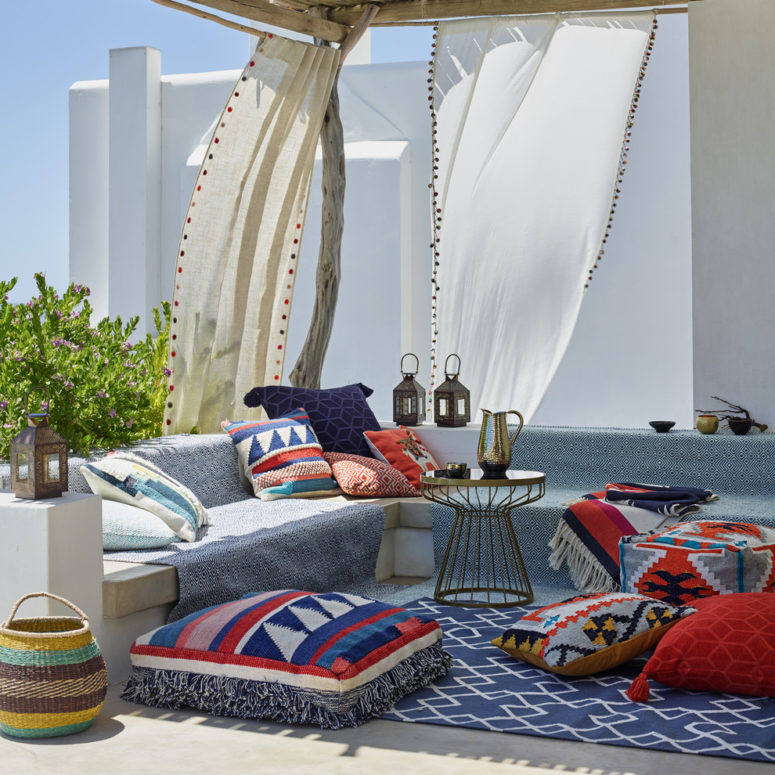 a bright Moroccan patio with a blue sofa, colorful printed pillows, Moroccan lanterns, baskets and airy curtains  (John Lewis & Partners)
