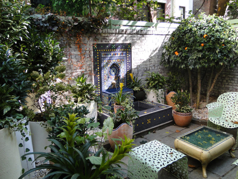 a gorgeous Moroccan patio with a traditional tiled Eastern fountain, mint laser cut furniture, potted greenery and citrus trees  (Christian Duvernois Landscape/Studio)