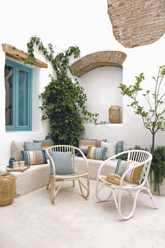 a Mediterranean beach patio with wicker furniture, bright pillows, potted plant and woven candle lanterns