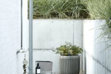 a Scandinavian outdoor shower with a concrete planter, stools and some accessories