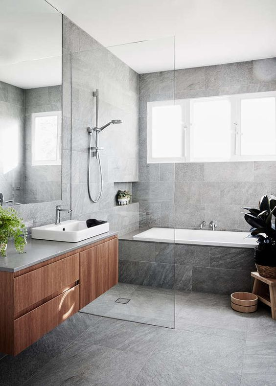 a bathroom done with grey marble tiles a floating vanity, a seamless glass shower door