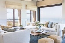 a beach living room in navy, blues and tan, with upholstered furniture, leather ottomans, tan Roman shades and printed pillows