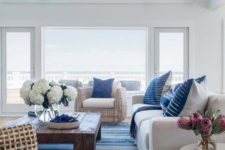 a beach living room with cool views, white upholstered and rattan furniture, a striped rug and printed pillows
