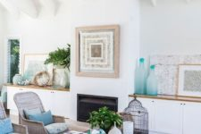 a beach living room with touches of blue and turquoise, printed furniture, a driftwood chandelier and an artwork