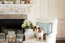 a beach mantel with a seashell and urchin wreath, potted blooms, large shells and a seashell and starfish garland