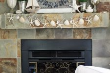 a beach mantel with a starfish and seashell garland, a boat, a starfish, some blooms and greenery