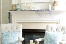 a beach mantel with bleu fishing net, starfish, a wrapped vase, a lantern and a driftwood crab artwork