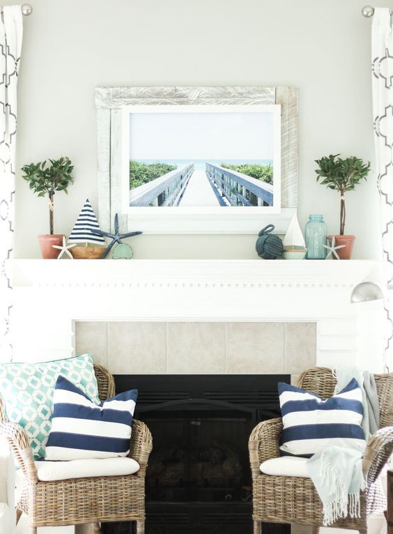 a beach mantel with mini boats, starfish, greenery in pots, a rope ball and a sea pier artwork