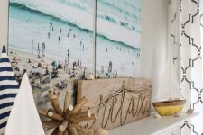 a beach mantel with seashells, two cute boats, a wooden sign and a gorgeous double beach artwork over it