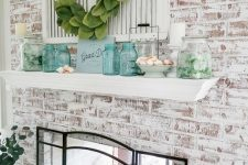 a beach mantel with turquoise jars, seashells in a bowl, jars with seaglass and a greenery wreath
