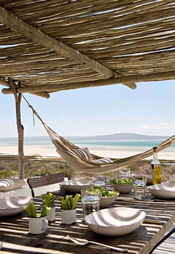 a beach patio with a roof, wooden and wicker furniture, a hammock, some tableware and a gorgeous sea view