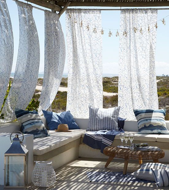 a beach patio with printed curtains, a bench with bright blue pillows, a wicker table and a candle lantern is very welcoming