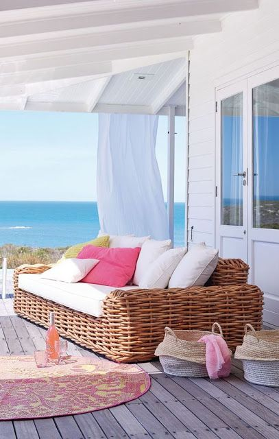 a beach terrace with a wooden deck, a large wicker sofa, bright and white pillows, baskets and a bright rug