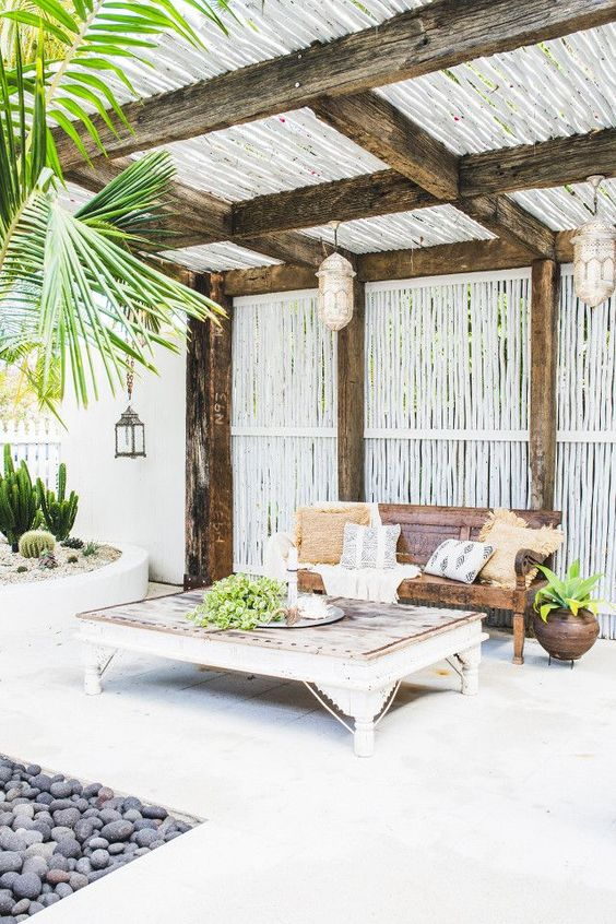 a beach terrace with vintage wooden furniture, Moroccan lamps, potted greenery, cacti and other plants is very relaxed