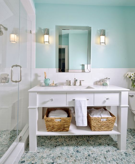 a beachy bathroom with a turquoise wall, a white vanity, baskets for storage for a welcoming space