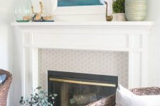 a beachy mantel with a seaside artwork, driftwood, blue beads, a green bottle, boxwood and a yarn wrapped bottle