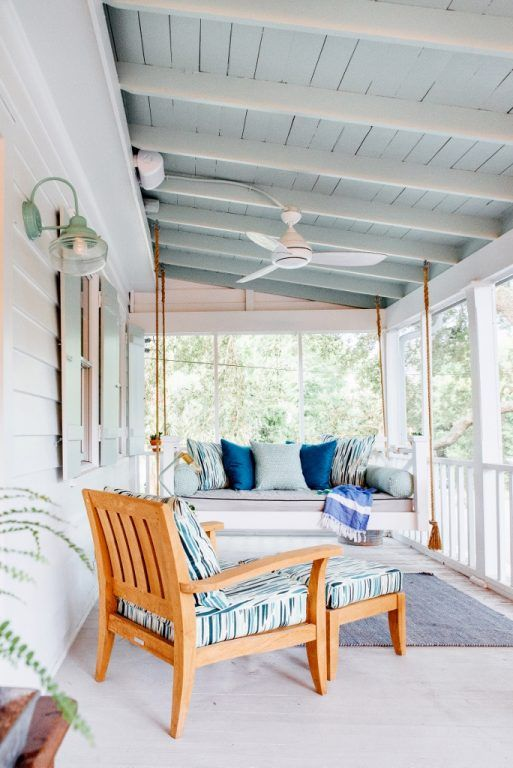 a beachy porch in light blues and white, with a hanging daybed and a lounger, some pillows, rugs and lamps