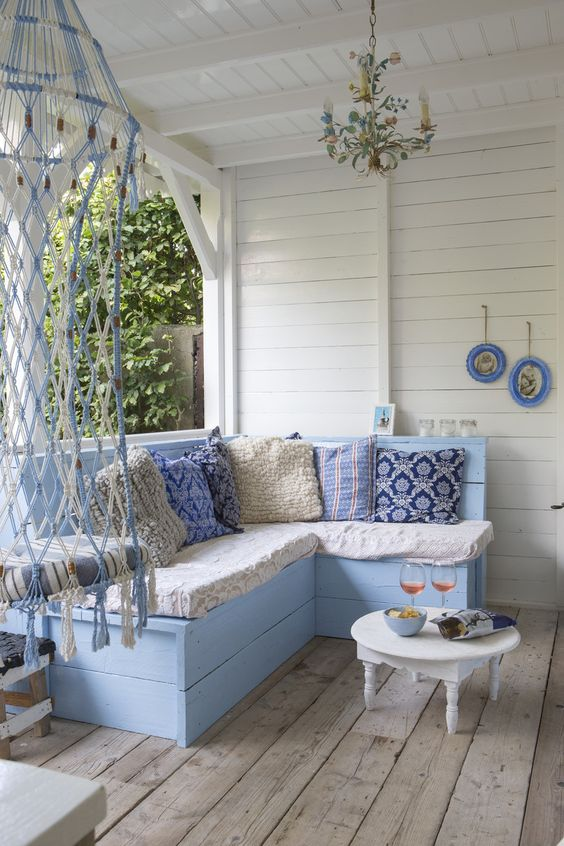 a beachy porch with vintage blue and white furniture, printed blue pillows, a whimsical chandelier and macrame is very welcoming