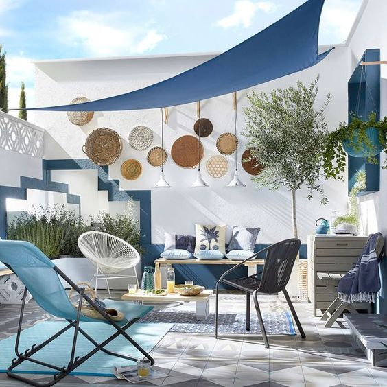 a blue seaside patio with rugs, bold woven chairs and stools, decorative plates, lamps and potted plants