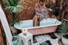 a boho chic outdoor bathroom with pebbles, potted plants, a pink tub and stools and ottomans