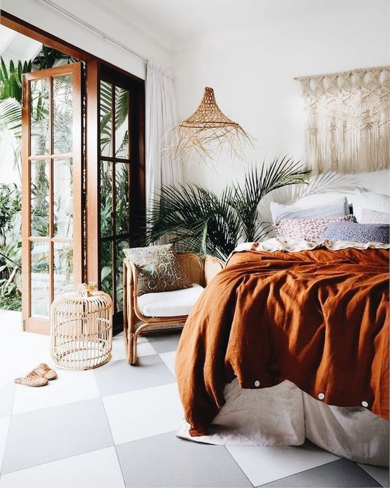 a boho tropical bedroom with a macrame wall hanging, a wicker pendant lamp, muted colored bedding and rattan furniture